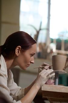Una giovane donna che dipinge la tazza e sembra coinvolta