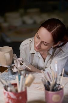 Una giovane donna che dipinge la ceramica e sembra coinvolta
