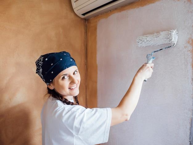 Giovane donna che dipinge le pareti della sua casa.