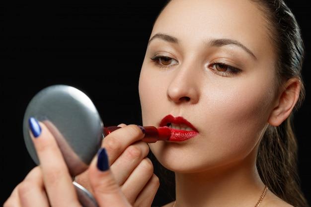 La giovane donna dipinge le labbra con rossetto rosso sul nero