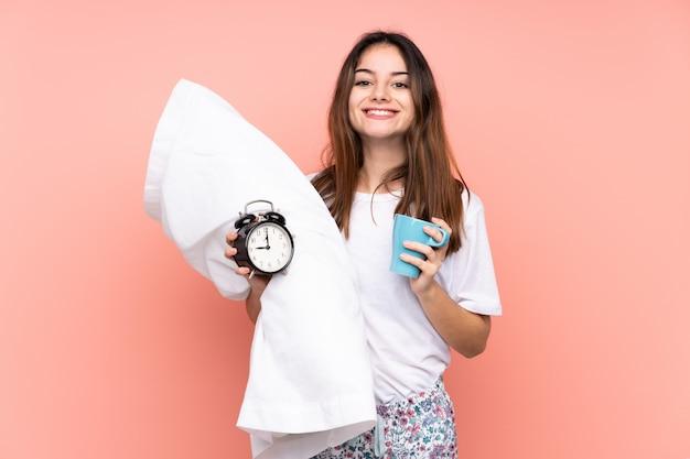 Giovane donna in pigiama e in possesso di orologio vintage isolato sulla parete rosa