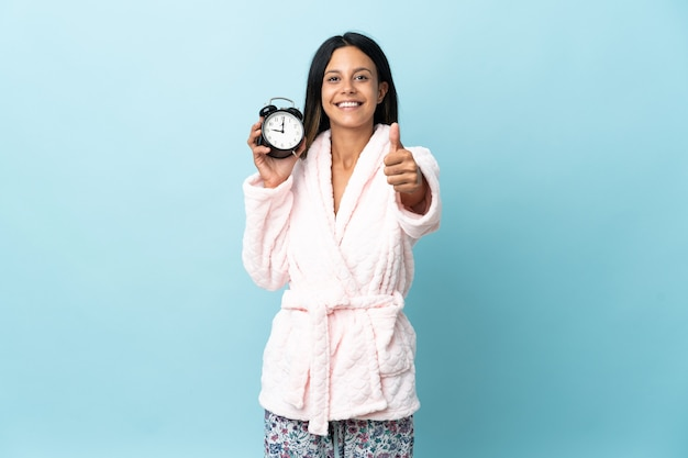 Giovane donna in pigiama su sfondo isolato in pigiama e tenendo l'orologio con il pollice in alto