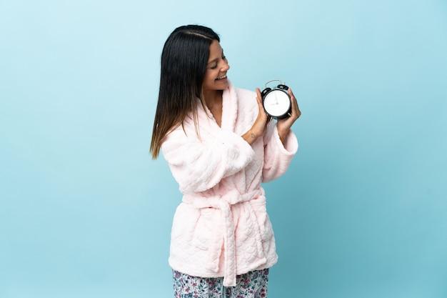 Giovane donna in pigiama sopra isolato in pigiama e tenendo l'orologio con felice espressione