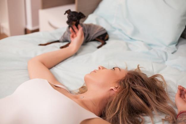 Giovane donna in pigiama seduta con il suo cagnolino di notte.