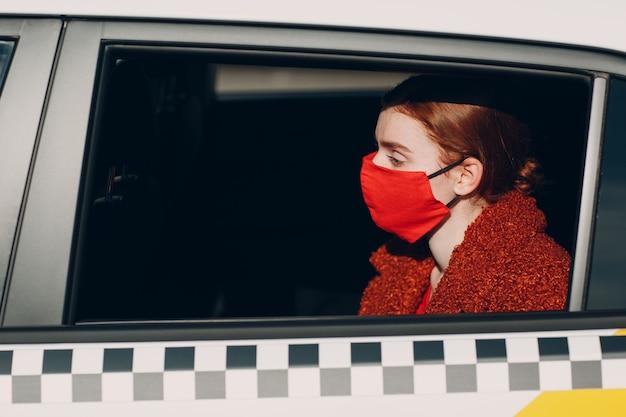 La giovane passeggera fa un giro in taxi durante la quarantena della pandemia di coronavirus indossa...