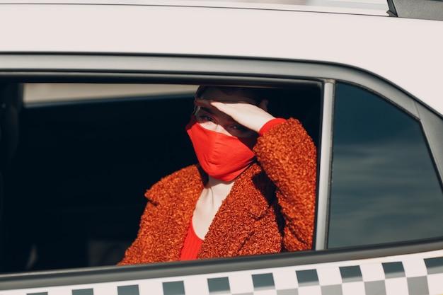 La giovane passeggera fa un giro in taxi durante la quarantena della pandemia di coronavirus. donna che indossa una maschera medica sterile. distanza sociale e sicurezza sanitaria nel concetto di trasporto.