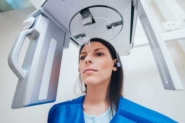 Paziente della giovane donna che sta nella macchina di raggi x.