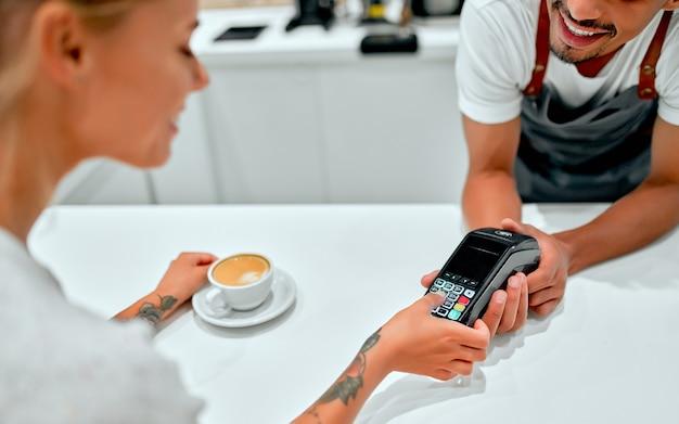 Giovane donna che paga con carta di credito al caffè. donna che entra perno di sicurezza nel lettore di carte di credito con barista maschio in piedi dietro la cassa al bar.