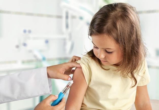 Il pediatra della giovane donna esegue una vaccinazione di una bambina. la ragazza tiene in mano una mascotte.