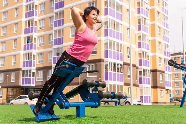Giovane donna che esegue esercizi di estensione della schiena nel cortile della città utilizzando una panca per l'iperestensione della macchina per esercizi da strada