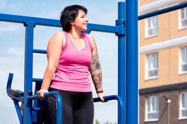 La giovane donna esegue gli esercizi all'aperto usando la macchina combinata di fitness di strada