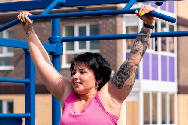 La giovane donna esegue gli esercizi all'aperto usando la barra orizzontale della strada