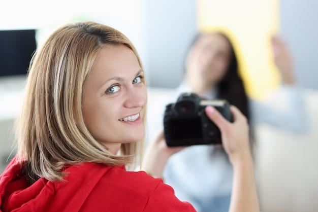 Fotografo della giovane donna che tiene la macchina fotografica nelle sue mani con la bruna a casa. passione per il concetto di hobby della fotografia.