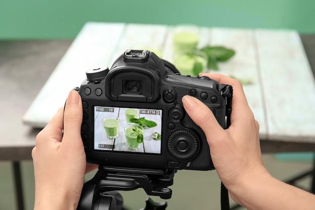 Giovane donna che fotografa il succo in studio fotografico, primo piano
