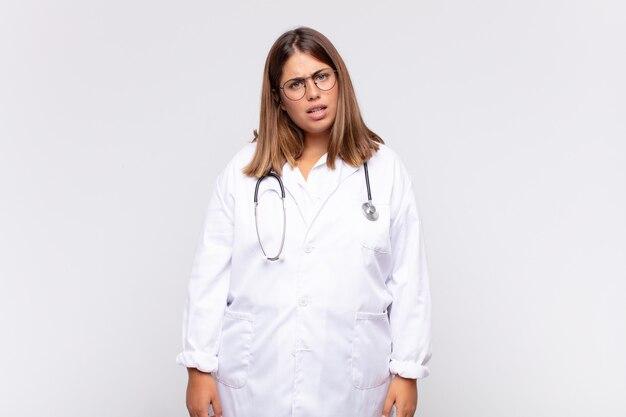 Il medico di una giovane donna si sente perplesso e confuso, con un'espressione stupita e sbalordita guardando qualcosa di inaspettato