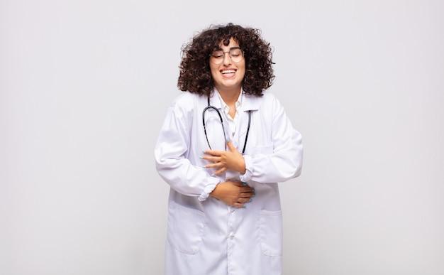 Medico di giovane donna che ride ad alta voce a uno scherzo esilarante, sentendosi felice e allegro, divertendosi