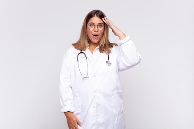 Giovane medico donna che sembra felice, stupita e sorpresa, sorridente e realizzando incredibili e incredibili buone notizie