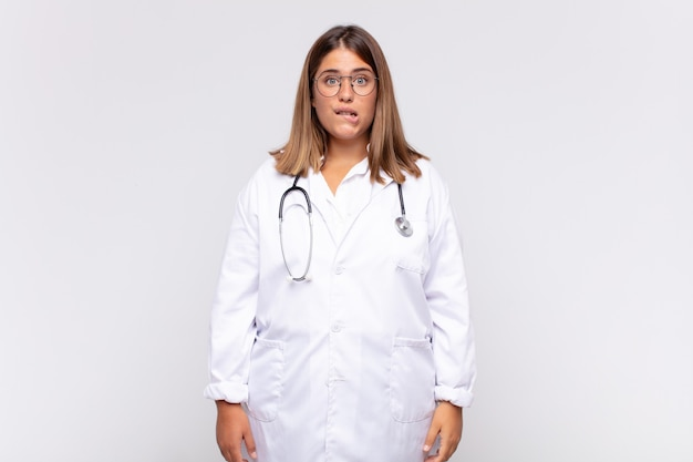Medico della giovane donna che sembra perplesso e confuso, mordendosi il labbro con un gesto nervoso, non conoscendo la risposta al problema
