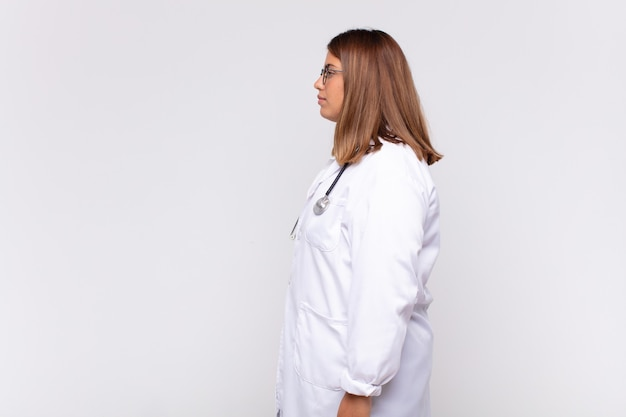 Medico della giovane donna sulla vista di profilo che cerca di copiare lo spazio davanti, pensare, immaginare o sognare ad occhi aperti