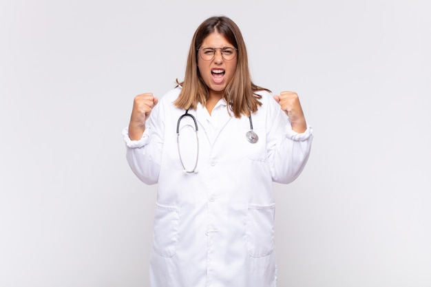 Medico della giovane donna che grida in modo aggressivo con un'espressione arrabbiata o con i pugni chiusi per celebrare il successo
