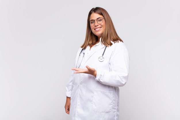 Medico della giovane donna che sorride allegramente, sentendosi felice e mostrando un concetto nello spazio della copia con il palmo della mano