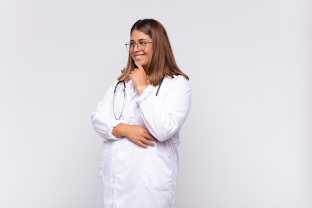 Medico della giovane donna che sorride con un'espressione felice e sicura con la mano sul mento, chiedendosi e guardando al lato