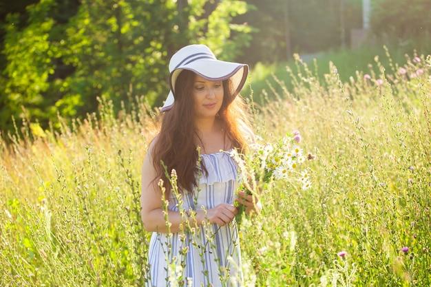 Giovane donna che raccoglie fiori nel prato nella sera d'estate