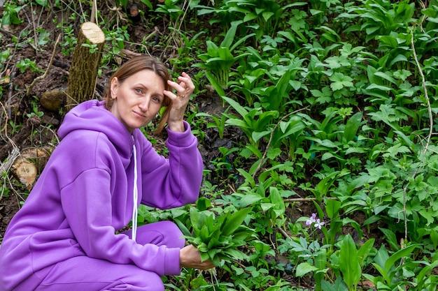 Giovane donna raccoglie foglie verdi di aglio selvatico nella foresta