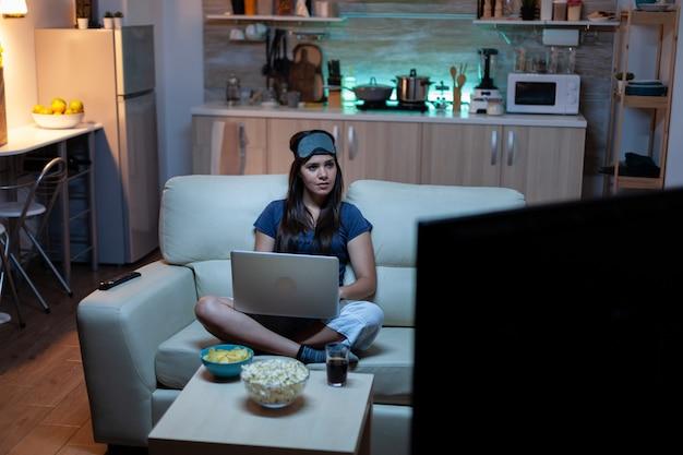 Giovane donna in pigiama che lavora di notte seduta sul divano con laptop. libero professionista che lavora davanti alla televisione lettura scrittura ricerca navigazione su notebook utilizzando la tecnologia internet