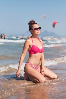 Giovane donna in bikini rosa che posa su una spiaggia.