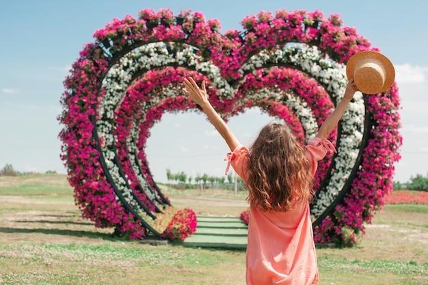 Giovane donna in abito rosa e cappello si alza e alza le mani sullo sfondo dell'amore degli archi del cuore dei fiori