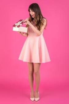 La giovane donna in un vestito rosa sta esaminando il presente