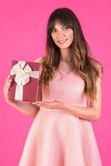 Giovane donna in un abito rosa con confezione regalo presente Foto Premium