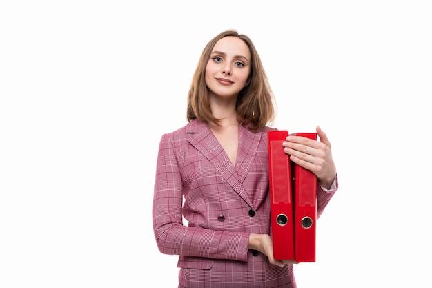 Una giovane donna con una giacca rosa tiene cartelle rosse con i documenti