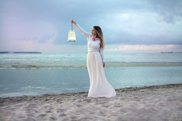 Giovane donna in abito lungo rosa con lanterna in piedi sulla spiaggia tramonto rosa al cielo