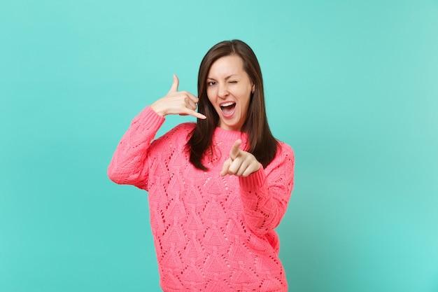 Giovane donna in maglione rosa che fa un gesto telefonico come dice di richiamarmi, puntando il dito indice che lampeggia isolato su sfondo blu della parete. persone sincere emozioni, concetto di stile di vita. mock up copia spazio.