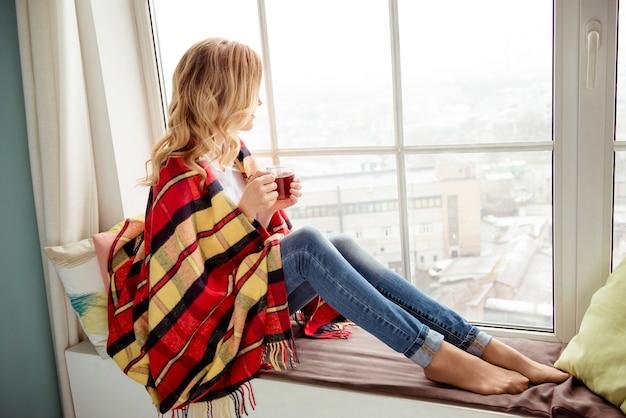 Giovane donna in plaid con una tazza di tè caldo seduto sul davanzale della finestra