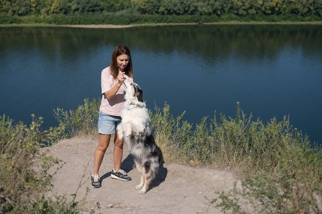 Gioco della giovane donna con il cane di merle blu del pastore australiano sulla sponda del fiume, estate. amore e amicizia tra uomo e animale. viaggia con animali domestici.