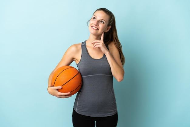 Giovane donna che gioca a basket isolato su sfondo blu pensando un'idea mentre guarda in alto