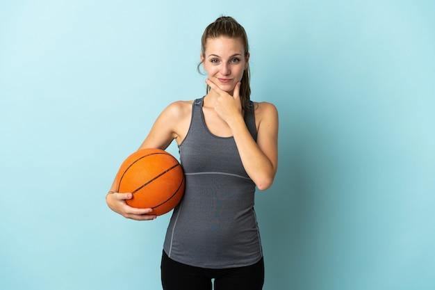 Giovane donna che gioca a basket isolato su sfondo blu pensando