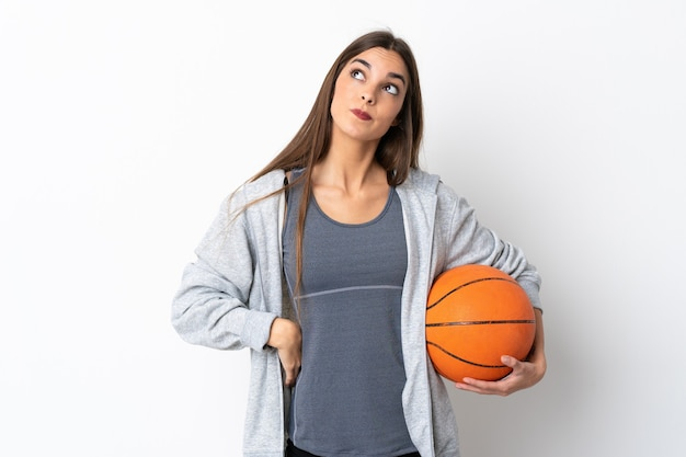 Giovane donna che gioca a basket isolato su sfondo bianco e guardando in alto