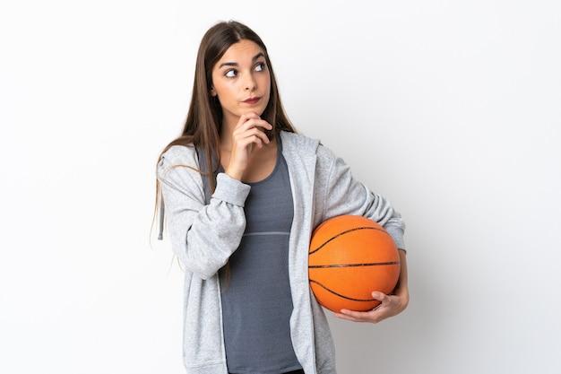 Giovane donna che gioca a basket isolato su sfondo bianco e alzando lo sguardo