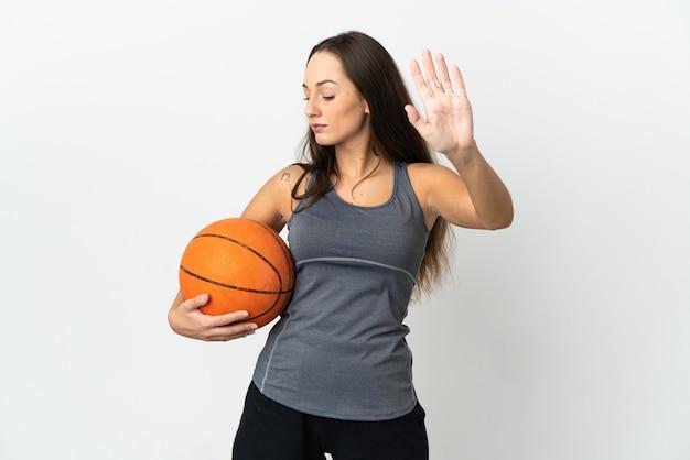 Giovane donna che gioca a basket su sfondo bianco isolato facendo gesto di arresto e deluso