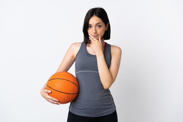 Giovane donna che gioca a basket isolato su sfondo bianco pensando