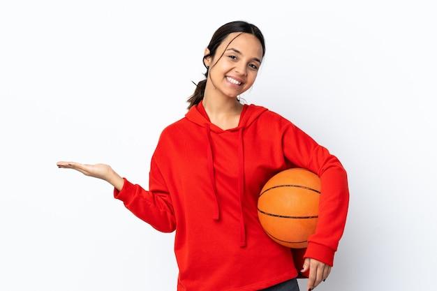 Giovane donna che gioca a basket su bianco isolato holding copyspace immaginario sul palmo per inserire un annuncio