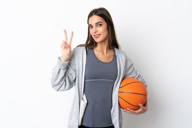 Giovane donna che gioca a basket isolato su bianco sorridendo e mostrando il segno di vittoria