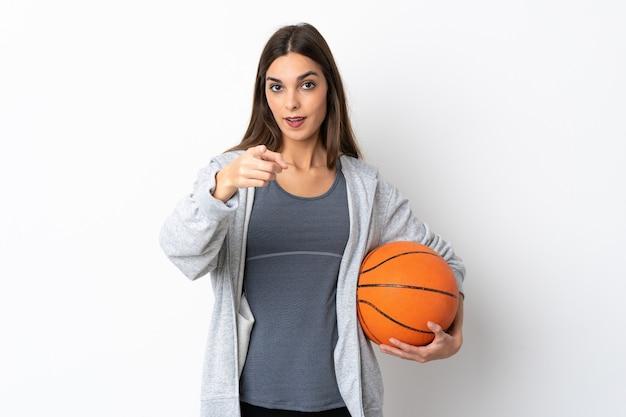 Giovane donna che gioca a basket isolato su bianco sorpreso e puntando la parte anteriore