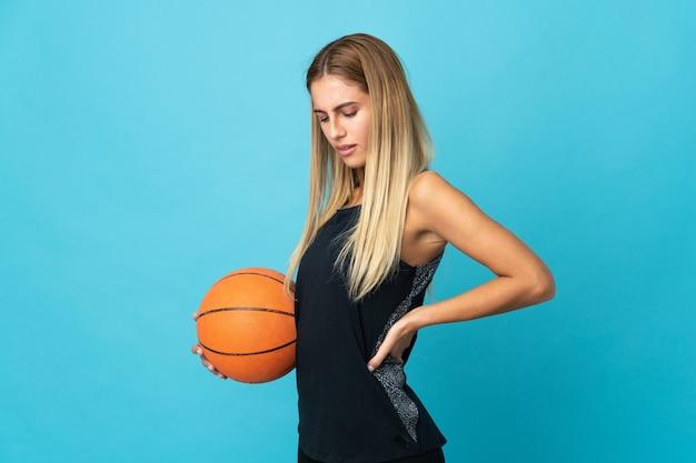 Giovane donna che gioca a basket isolato sul muro bianco che soffre di mal di schiena per aver fatto uno sforzo