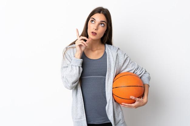 Giovane donna che gioca a basket su bianco pensando un'idea puntando il dito verso l'alto