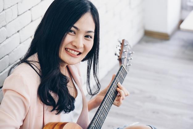 Giovane donna a suonare la chitarra in salotto